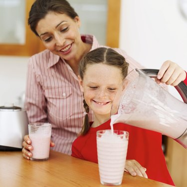 Young mother and a young girl (8-10) pouring out strawberry milk shake from a blender into a glass