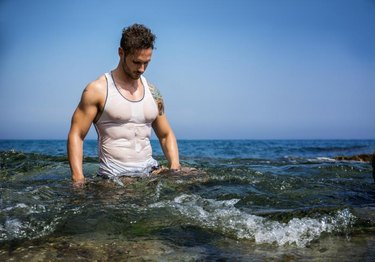 Attractive, muscular man in the sea with wet t-shirt on, serious expression.