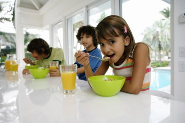 Three kids (8-10) at table, having breakfast, portrait