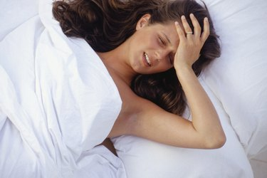 Young woman lying in bed, hand on head, elevated view