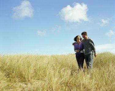 Mature couple walking through grass, smiling