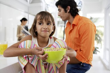 Family at breakfast table, girl (8-10) holding bow of cereal