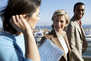 Two businesswomen and man by sea, smiling