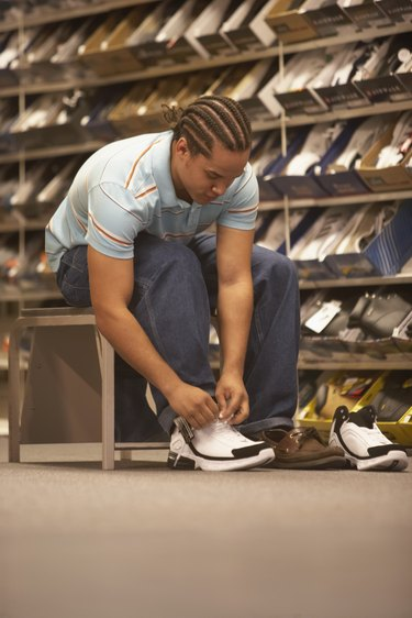 Teenage boy trying on shoes in a shoe store