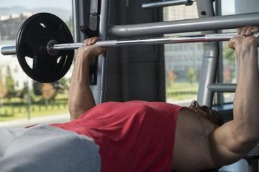 Young Men In Gym Exercising On The Bench Press