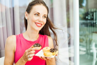 happy smiling woman eating a donut