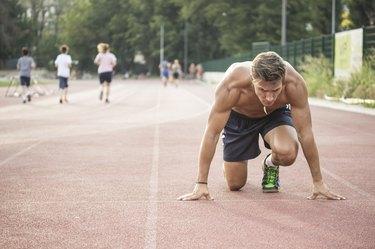 Sprinter at start position, kneeling, muscular body.