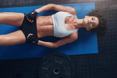 Overhead shot of woman relaxing after exercise session with a heavy weight plate on floor. Top view of young woman lying on exercise mat in gym.