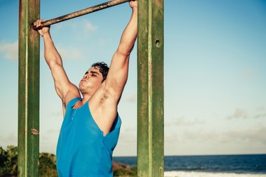 brazilian  athlete outdoor at chin-up rack at beach