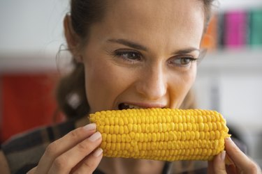 young woman eating boiled corn