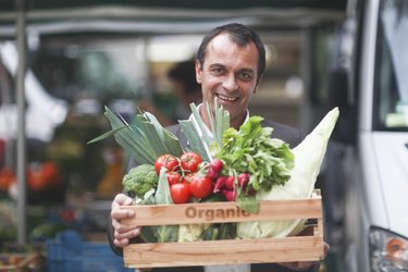 Portrait of mature man holding box of vegetables from market