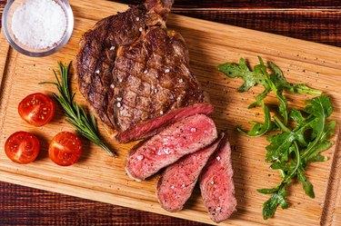 Ribeye steak with arugula and tomatoes.