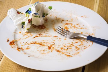 Empty dish after food on the table with wooden background
