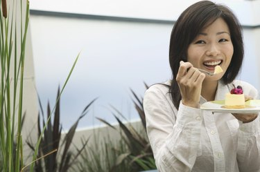 Portrait of a young woman eating from a plate with a fork