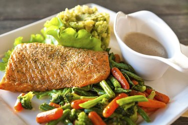 Grilled salmon fillet with potato-spinach mash and vegetables.