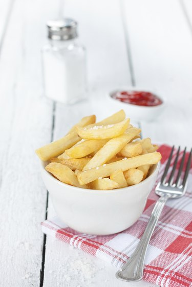 French fries in a white bowl on table