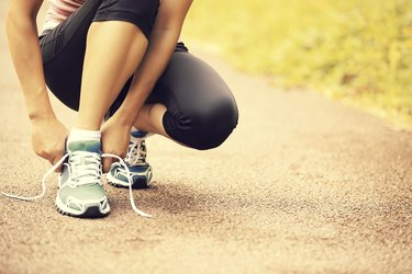 woman runner tying shoelaces on trail