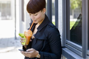 young woman drinking smoothie using mobile phone