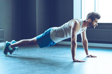 Full length of young handsome man in sportswear doing push-up at gym