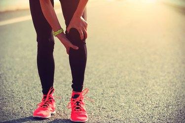 A female road runner holding her injured knee
