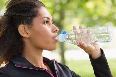 Close up side view of tired woman drinking water in park