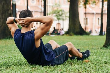 Sportsman doing crunches on grass in park