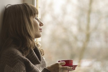Beautiful girl dreaming with cup of coffee