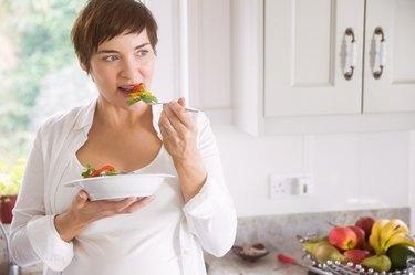 Pregnant woman having bowl of salad