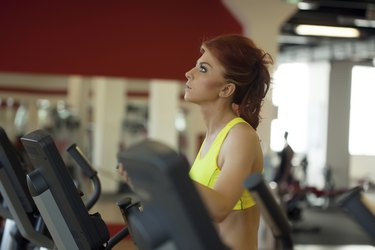 Pretty red-haired girl exercising on treadmill