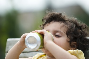 A small child drinking from a soda can feeling effects of caffeine