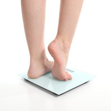 Beautiful woman legs on a scale
