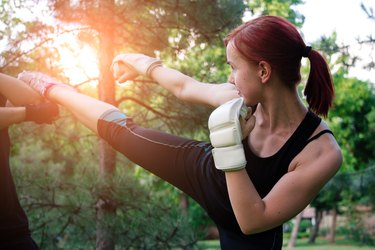 Young woman boxer workout on outdoors on sunny summer day.