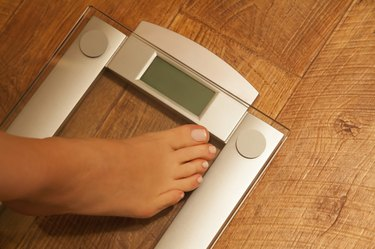 Stepping on weight scale.