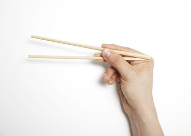 Man's hand gripping chopsticks over white background