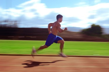 Man Running on Track With Shirt Off