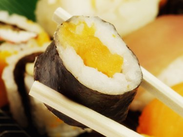A sushi roll held with a pair of chopsticks