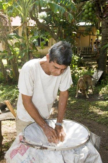 man making coconut oil Nicaragua Corn Island Central America