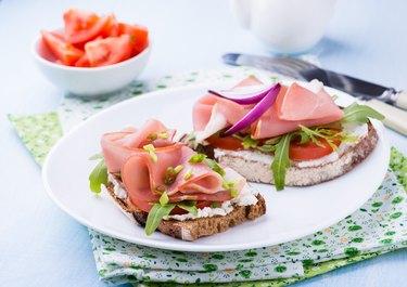 Open sandwiches with ham, tomato and arugula