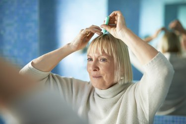 senior woman checking hairline for hair loss