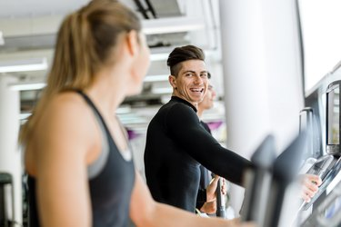 Man and beautiful woman using a stepper in a gym