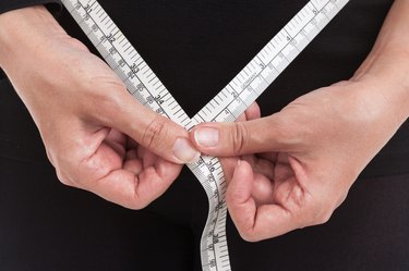 Obese woman is measuring her waist by measuring tape.