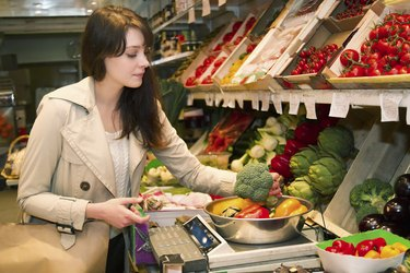 Young woman who weighs vegetables that it is buying