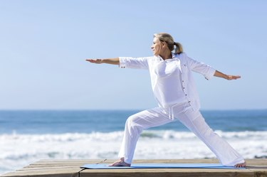 mature woman yoga exercise on beach