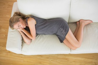 Casual blonde lying on couch sleeping
