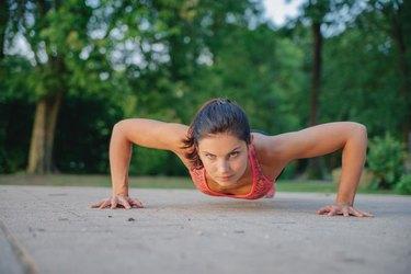 fitness girl doing pushups in park