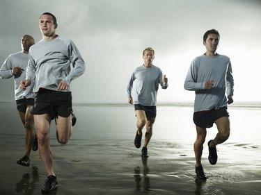 Four men running on beach by ocean