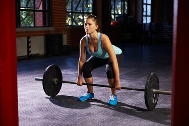 Woman In Gym Preparing To Lift Weights