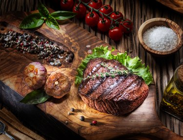 Beef steaks with spices on a wooden tray.