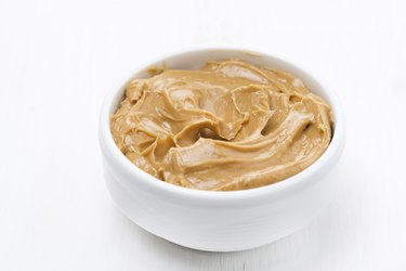 bowl of peanut butter on white wooden table