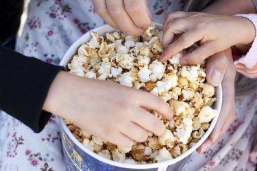 Children eat popcorn out of a paper bucket, close-up